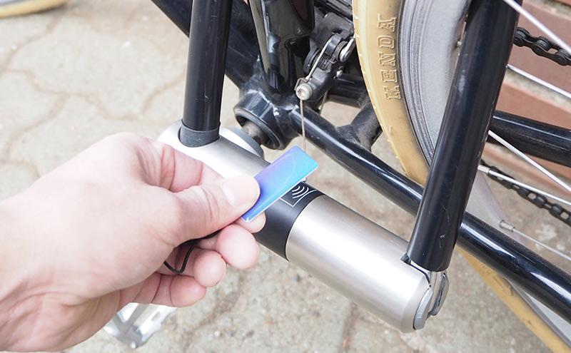 専用のカードキーで自転車の鍵を開ける人
