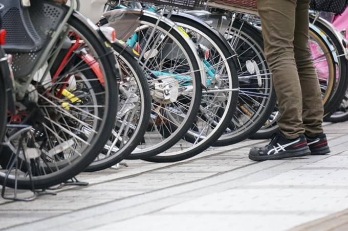 駐輪場の自転車と自転車を物色している人